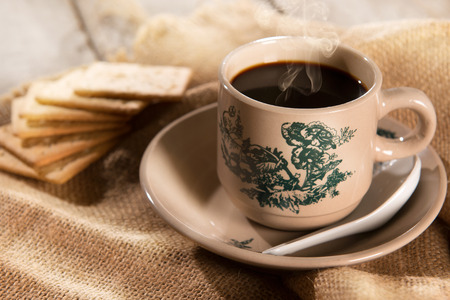 Steaming traditional oriental Chinese kopitiam style dark coffee in vintage mug and saucer with soda crackers. Fractal on the cup is generic print. Soft focus setting with dramatic ambient light on dark wooden background. Standard-Bild