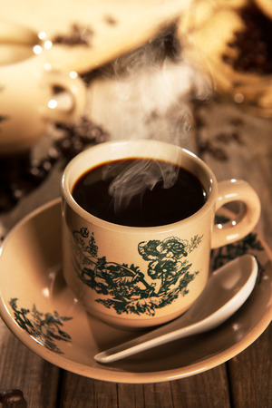ambient light: Steaming traditional Chinese nanyang style coffee in vintage mug and saucer with coffee beans. Fractal on the cup is generic print. Soft focus setting with dramatic ambient light on dark wooden background.