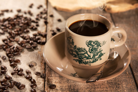 kopitiam: Steaming traditional Chinese Hainan style coffee in vintage mug and saucer with coffee beans. Fractal on the cup is generic print. Soft focus setting with dramatic ambient light on dark wooden background.