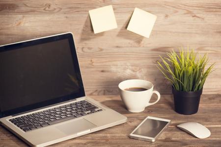 Houten bureau met laptop, een kop hete koffie, muis, smartphone en potplanten, in vintage afgezwakt.