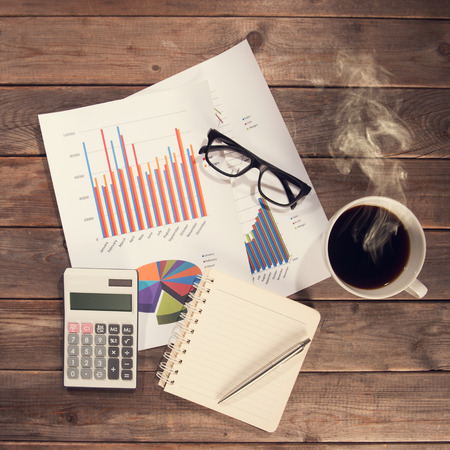 place of work: Top view workspace with booklet, pen, glasses, cup of coffee and graphs. Wooden table background in vintage toned. Stock Photo