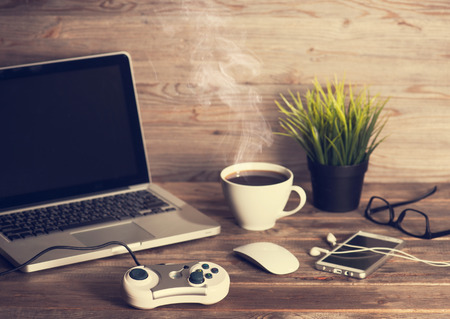 Wooden office workplace, table with laptop, online games controller, cup of hot coffee, mouse, glasses, smartphone, earphones and pot plant, in dramatic light vintage toned.