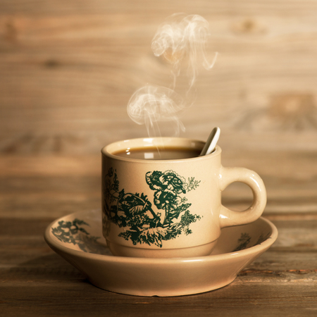 Close-up dampende traditionele oosterse Chinese koffie in vintage mok en schotel. Fractal op de beker is generiek druk. Soft focus instelling met dramatische omgevingslicht op donkere houten achtergrond.