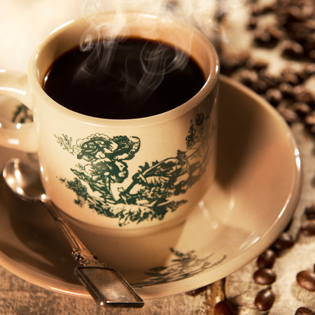 kopitiam: Steaming traditional Hainanese style black coffee in vintage mug and saucer with coffee beans. Fractal on the cup is generic print. Soft focus setting with dramatic ambient light on dark wooden background. Stock Photo
