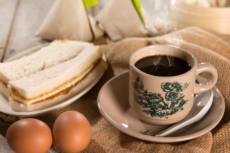 kopitiam: Traditional kopitiam style Malaysian coffee in vintage mug and saucer and breakfast. Fractal on the cup is generic print. Soft focus dramatic ambient light over wood table. Stock Photo