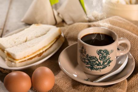 Traditionele kopitiam stijl Maleisische koffie in vintage mok en schotel en ontbijt. Fractal op de beker is generiek druk. Soft focus dramatische omgevingslicht over houten tafel. Stockfoto