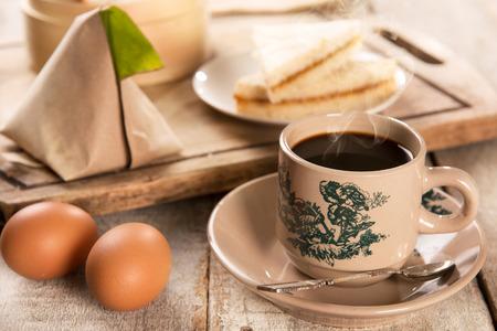 Traditionele kopitiam stijl Maleisische koffie in vintage mok en schotel en ontbijt met ochtend zonlicht. Fractal op de beker is generiek druk. Soft focus dramatische omgevingslicht over houten tafel.