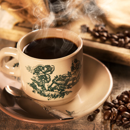 steaming coffee: Steaming traditional Hainan style dark coffee in vintage mug and saucer with coffee beans. Fractal on the cup is generic print. Soft focus setting with dramatic ambient light on dark wooden background.