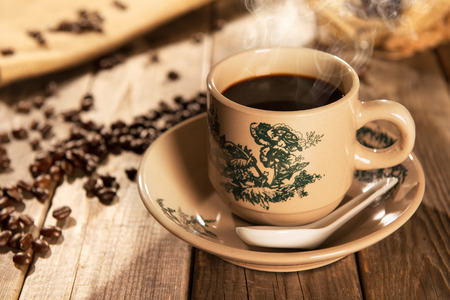 kopitiam: Steaming traditional Chinese style coffee in vintage mug and saucer with coffee beans. Fractal on the cup is generic print. Soft focus setting with dramatic ambient light on dark wooden background.