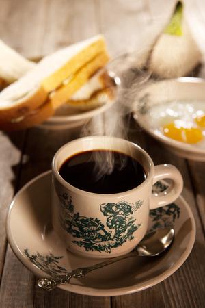 Traditionele kopitiam-stijl Maleisische koffie en ontbijt met ochtendzonlicht. Fractal op de beker is een generieke afdruk. Soft focus dramatisch omgevingslicht over houten tafel.