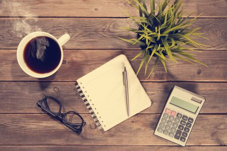 Business analysis concept. Top view workspace with booklet, pen, calculator, glasses and coffee mug. Wooden table background vintage toned. Archivio Fotografico