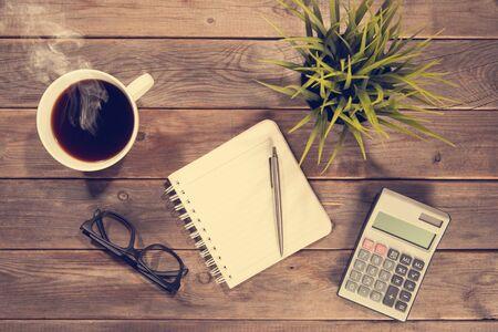 Business analyse concept. Bovenaanzicht werkruimte met boekje, pen, rekenmachine, glazen en bekers. Houten tafel achtergrond vintage afgezwakt.