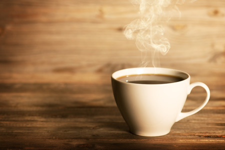 Steaming coffee in white cup in soft focus setting with dramatic ambient light, over dark wooden background. Imagens
