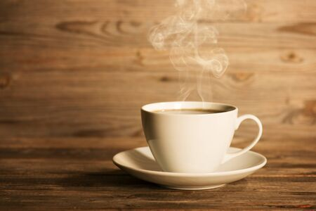 Steaming coffee in white mug and saucer in soft focus setting with dramatic ambient light, over dark wooden background.