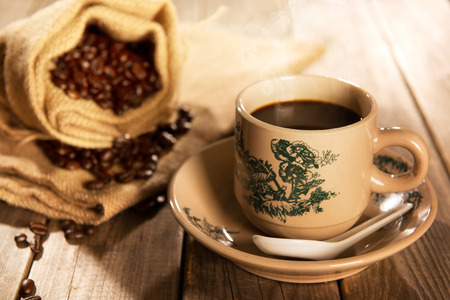 ambient light: Traditional Chinese style coffee in vintage mug and saucer with coffee beans. Fractal on the cup is generic print. Soft focus setting with dramatic ambient light on dark wooden background. Stock Photo