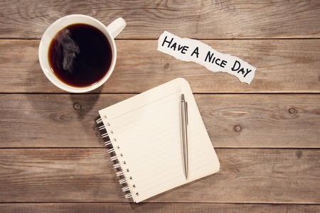 note booklet: Top view work space with booklet, pen, cup of coffee and note message Have A Nice Day. Wooden table background in vintage toned. Stock Photo