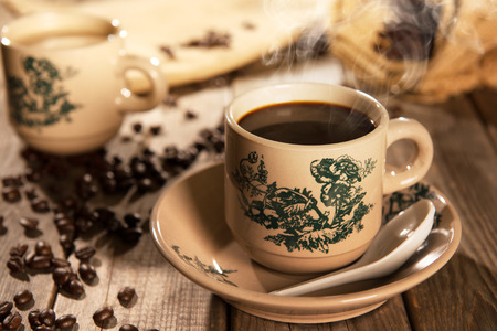 yang style: Steaming traditional Chinese nan yang style coffee in vintage mug and saucer with coffee beans. Fractal on the cup is generic print. Soft focus setting with dramatic ambient light on dark wooden background.