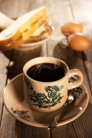Traditional Singapore Chinese style coffee in vintage mug and saucer with breakfast. Fractal on the cup is generic print. Soft focus dramatic ambient light over wood table.