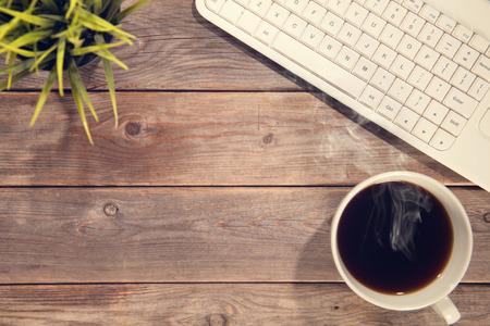 planta de cafe: Vista superior del espacio de trabajo con teclado de computadora, taza de café y planta de maceta. Fondo de la tabla de madera en la vendimia entonado.