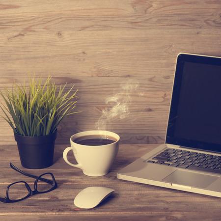 Houten kantoor tafel met laptop, een kop hete koffie, muis, glazen en potplant, in dramatische licht vintage afgezwakt.
