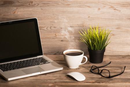 ノート パソコン、ホット コーヒー、マウス、メガネ、鍋植物は劇的な光のビンテージのカップで木製の職場はトーンダウン。