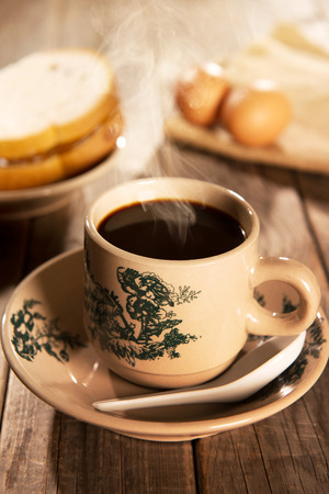 kopitiam: Traditional Chinese style coffee in vintage mug and saucer with breakfast. Fractal on the cup is generic print. Soft focus dramatic ambient light over wood table.