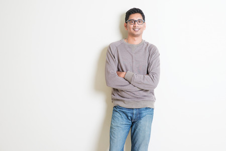 Portrait of handsome casual Indian male arms crossed and smiling, standing on plain background with shadow, copy space at side. Standard-Bild