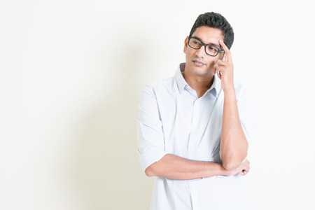 Portrait of handsome casual business Indian man thinking with serious face expression, standing on plain background with shadow, copy space at side.