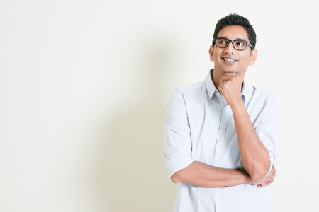 portrait: Portrait of handsome casual business Indian man smiling and thinking, eyes looking upwards, standing on plain background with shadow, copy space at side. Stock Photo