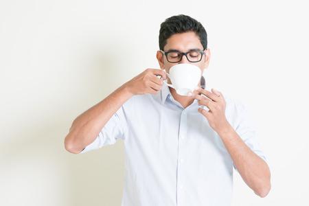 tomando leche: Retrato de guapo chico indio casual de negocios relajarse y beber una taza de café caliente, de pie en el fondo plano con la sombra, copia espacio en el costado.