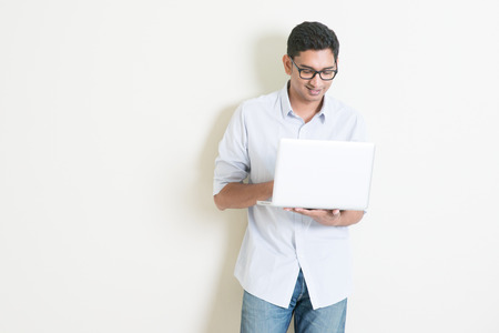 native american man: Portrait of handsome casual business Indian man using laptop computer, standing on plain background with shadow, copy space at side. Stock Photo