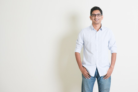 studio portrait: Portrait of handsome casual business Indian guy smiling, hands in pocket, standing on plain background with shadow, copy space at side.