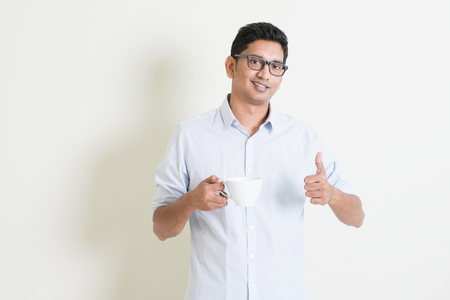 Portrait of handsome casual business Indian guy drinking a cup hot coffee and giving thumb up, standing on plain background with shadow, copy space at side. Stock Photo
