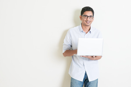Portrait of handsome casual business Indian guy using laptop computer, standing on plain background with shadow, copy space at side.