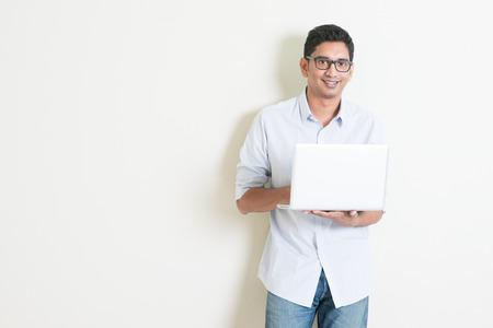 Portret van knappe casual business Indiase jongen met behulp van laptop computer, staande op duidelijke achtergrond met schaduw, kopie ruimte aan de zijkant. Stockfoto