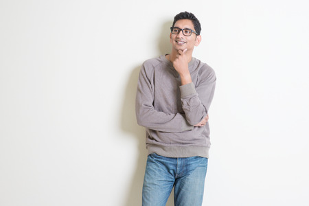 Portrait of handsome casual Indian male thinking and smiling, standing on plain background with shadow, copy space at side.