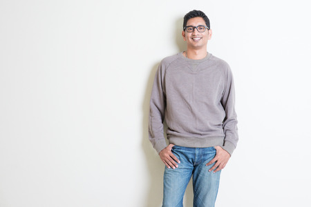Portrait of handsome casual Indian male smiling, standing on plain background with shadow, copy space at side.