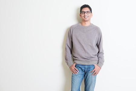 Portret van knappe toevallige Indiase man glimlachen, staande op effen achtergrond met schaduw, kopiëren ruimte aan de zijkant.