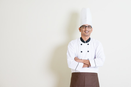 young guy: Portrait of handsome Indian male chef in uniform smiling, standing on plain background with shadow, copy space at side. Stock Photo