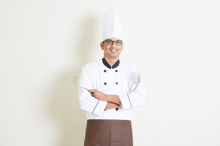 white men: Portrait of handsome Indian male chef in uniform hand holding kitchen tools and smiling confidently, standing on plain background with shadow, copy space on side.