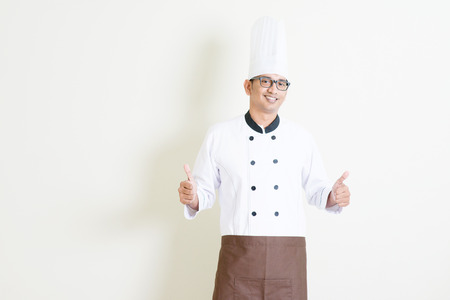 young guy: Portrait of handsome Indian male chef in uniform and hat thumbs up and smiling, standing on plain background with shadow, copy space on side.