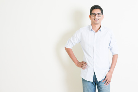 business model: Portrait of handsome casual business Indian male smiling, standing on plain background with shadow, copy space at side. Stock Photo