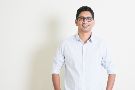 indian student: Portrait of handsome casual business Indian man smiling and looking at camera, standing on plain background with shadow, copy space at side.