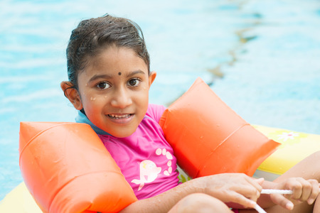 float: Cute Indian girl learning swimming in pool. Asian kid in swimmer class with float bands. Stock Photo
