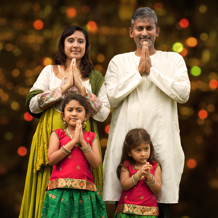 celebrating female: Indian family greeting on Diwali, festival of lights, inside a temple.