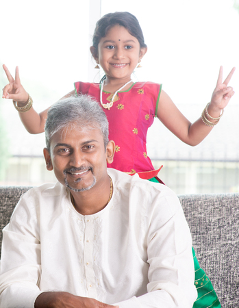 indian ethnicity: Happy Indian family at home. Asian girl showing peace hand sign. Adults and kids indoor lifestyle.