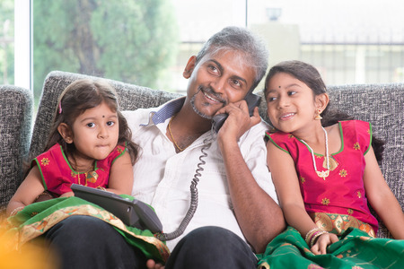 taking a wife: Husband making a phone call to wife while taking care of children at home. Asian Indian family at home.