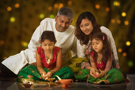 Indische familie in traditionele sari verlichting olielamp en vieren Diwali, fesitval van lichten in een tempel. Meisje handen holding olielamp binnenshuis.