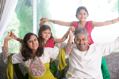 south indian: Happy Indian family at home. Asian parents playing with their kids, sitting on sofa. Parents and children indoor lifestyle.