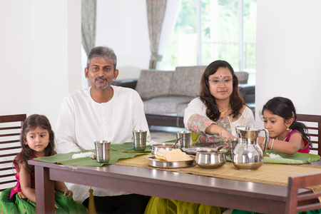 india food: Indian family dining at home. Photo of India people eating rice on dining table. Traditional home cook meal. Stock Photo